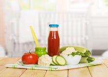 Flaskan av tomatfruktsaft och grönsakpuré packar ihop onbackgroundkök Royaltyfri Bild