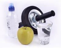 Flaskan av vatten, det gröna äpplet, exponeringsglas av vatten och rullen rullar fo Arkivbilder