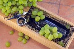 Flaskan av vin packas i träbehållare och druvor Arkivfoton