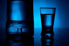 Flaskan av vodka med exponeringsglas tände med det blåa panelljuset Royaltyfri Fotografi