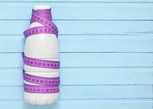 Flaskan av yoghurt som slås in i en linjal på en rosa trätabell, bantar arkivfoto