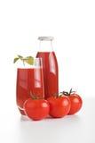 flaskan bär fruktt den glass fruktsafttomaten Arkivfoto