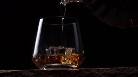 Flaskan hälls in i ett exponeringsglas av whisky med is på en svart bakgrund lager videofilmer