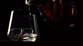 Flaskan hälls in i ett exponeringsglas av whisky med is på en svart bakgrund stock video