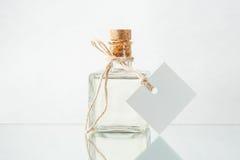 Flaskan med genomskinlig flytande och tömmer etiketten på ljuset tillbaka Royaltyfria Foton