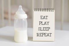 Flaskan med mjölkar för behandla som ett barn, och notepaden i bakgrunden av behandla som ett barn säng Nyfött behandla som ett b Arkivfoton