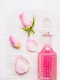 Flaskan med rosvatten och rosa färgrosen slår ut på vitt trä Royaltyfri Foto