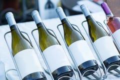 Flaskexponeringsglas med vitt vin i rad på tabellen arkivfoton