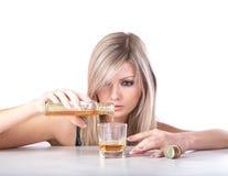 flaskflickaexponeringsglas häller whisky royaltyfri foto