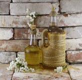 Flaskor av äppeljuice med blommor Fotografering för Bildbyråer