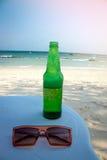 Flaskor av öl på stranden arkivfoton