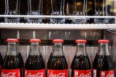 Flaskor av coca-cola den berömda drinken i kylen Arkivfoton