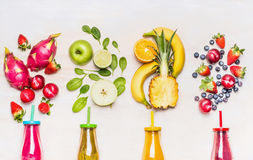 Flaskor av fruktsmoothies med olika ingredienser på vit träbakgrund, bästa sikt, slut upp Royaltyfri Bild