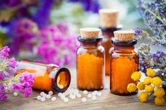 Flaskor av homeopatiska små kulor och läkaörter royaltyfri bild