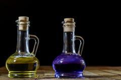 Flaskor av kulör flytande på ett träköksbord TräTabl Arkivfoton