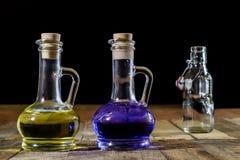 Flaskor av kulör flytande på ett träköksbord TräTabl Royaltyfria Bilder