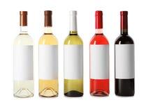 Flaskor av läckra viner med tomma etiketter på vit bakgrund Royaltyfri Foto