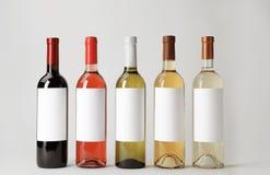 Flaskor av läckra viner med tomma etiketter på vit bakgrund Royaltyfri Bild