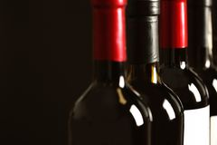 Flaskor av olika viner på mörk bakgrund Dyr samling royaltyfria bilder