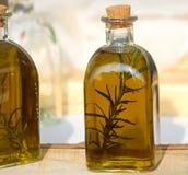 Flaskor av olivolja som kryddas med lösa rosmarin Arkivbild