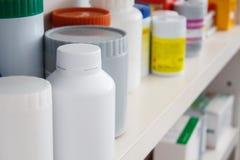 Flaskor av preventivpillerar som är ordnade på hylla på apoteket Royaltyfri Fotografi