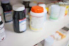 Flaskor av preventivpillerar som är ordnade på hylla på apoteket Arkivfoto