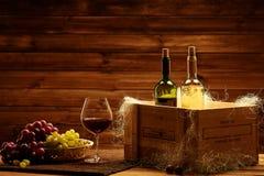 Flaskor av rött och vitt vin, exponeringsglas och druvan på ett träinter- royaltyfri fotografi