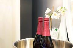 Flaskor av rött vin på is i en glass behållare Bredvid blommorna på spegelbakgrunden royaltyfria foton