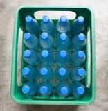 Flaskor av vatten i grön spjällåda Royaltyfri Foto