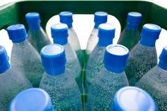 Flaskor av vatten i grön spjällåda Arkivfoton