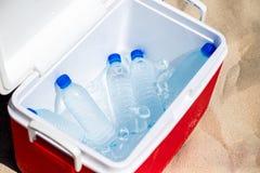 Flaskor av vatten i isasken på stranden Arkivfoto