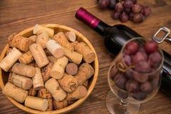 Flaskor av vin, exponeringsglas av vin, druvor och korkvin Arkivbilder
