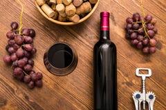 Flaskor av vin, exponeringsglas av vin, druvor och korkvin Arkivfoton