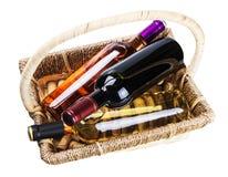 Flaskor av vin i en korg som isoleras på en vit Arkivbild