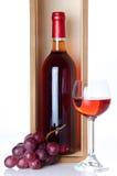 Flaskor av vin i en träask med ett exponeringsglas av vin och röd gra Royaltyfri Bild