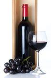 Flaskor av vin i en träask med ett exponeringsglas av vin och svartG Royaltyfri Bild