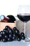 Flaskor av vin i en träask med ett exponeringsglas av vin och svartG Royaltyfri Foto