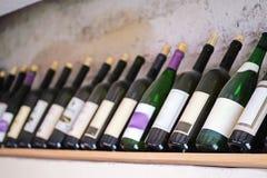 Flaskor av vin på en trähylla i restaurangen Royaltyfri Bild