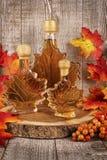 Flaskor för lönnsirap på en träplanka royaltyfri fotografi