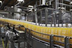 Flaskor för orange fruktsaft på transportör, i att buteljera växten royaltyfri fotografi