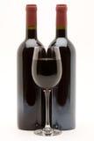flaskor fyllde rött vinwineglassen royaltyfri bild