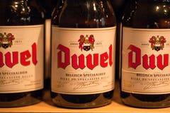Flaskor med öl Duvel i lokalt lager med produkter av olika populära bryggerin Arkivfoton