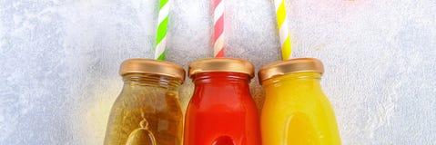 Flaskor med den nya apelsinen, äpplet, tomatfruktsaft och kulöra tubules på grånar den konkreta tabellen Frukter och grönsaker om royaltyfri foto