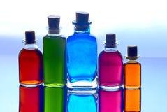Flaskor med flytande av många färgar Arkivbilder