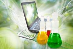 flaskor med flytande och bärbara datorn i laboratoriumslut upp Royaltyfri Bild