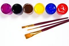 Flaskor med gouache målar och borstar för konstnärliga målningar Royaltyfri Bild