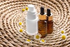 Flaskor med kosmetiska produkter och nya kamomillblommor Royaltyfria Foton