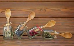 Flaskor med kulöra peppar och träskedar Arkivbild