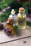 Flaskor med nödvändig arom för granträdet oljer på åldrig träbackg royaltyfri bild