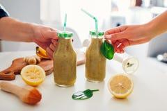 Flaskor med spenat- och banansmoothien med ingredienser Folk som rymmer drinkar Den sunda detoxen bantar arkivfoto